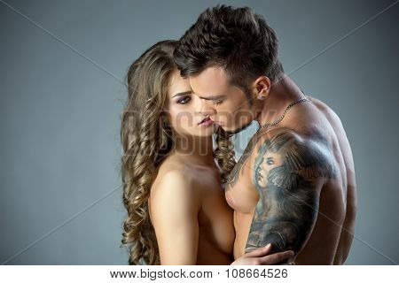 Charming model lovingly looks at tattooed man