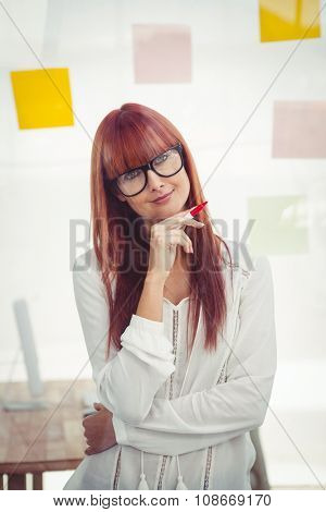 Attractive smling hipster woman thinking in her office