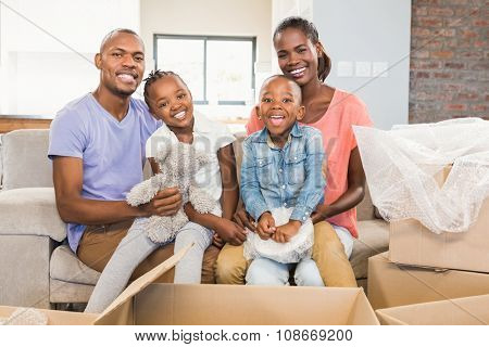 Casual happy family posing with box in living room