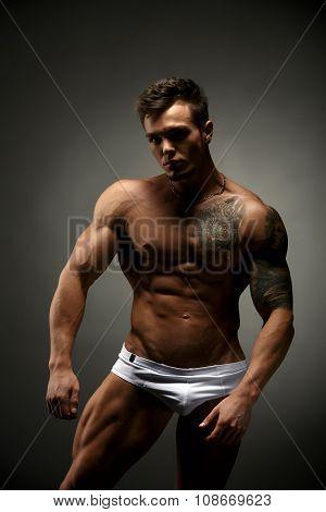 Bodybuilder advertises underwear. Studio photo