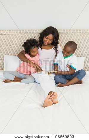 Mother and children reading in bed at home