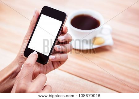 Overhead of feminine hands using smartphone with coffee and biscuit on table