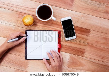 Overhead of feminine hands writing on agenda with coffee, smartphone and muffin on table