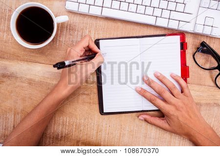 Businesswoman writing on diary on desk at work