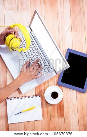 Overhead of feminine hands typing on laptop and holding headphones with stuff on desk