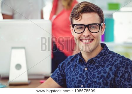 Smiling creative businessman working near co workers in casual office