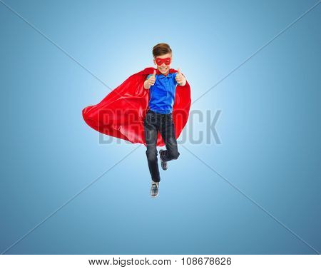 imagination, gesture, childhood, movement and people concept - boy in red super hero cape and mask flying in air and showing thumbs up over blue background
