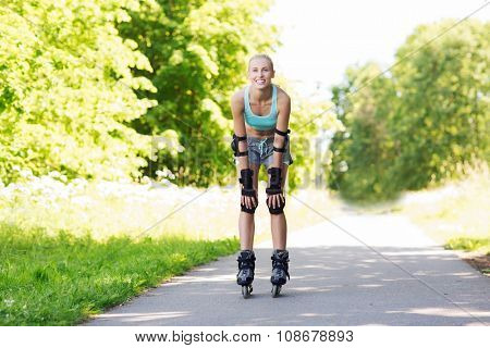 fitness, sport, summer, rollerblading and healthy lifestyle concept - happy young woman in rollerskates and protective gear riding outdoors