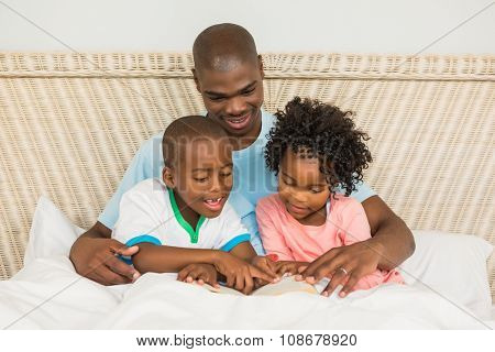 Father reading a book with his children in bed