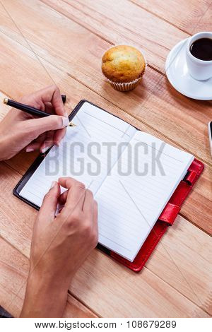 Overhead of feminine hands writing on agenda with espresso, smartphone and muffin on table
