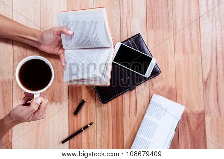 Overhead of feminine hands holding a book and coffee with agenda, newspaper and smartphone on table