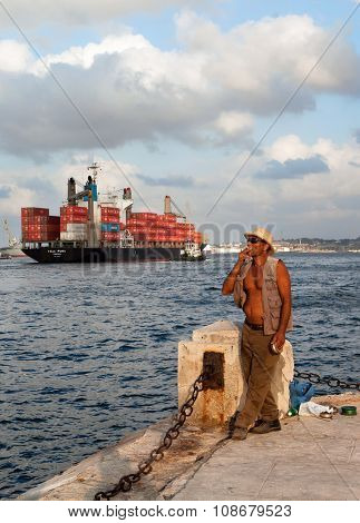 HAVANA, CUBA - MAY 19: Unknown Cuban fisherman catches a fish at the Malecon seawall on May 19, 2013 in Havana, Cuba. Fishing in the city helps to replenish the meager diet of poor people in Havana