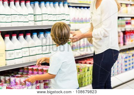 Back view of mother and son looking at the supermarket fridge