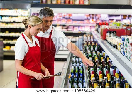 Serious colleagues with clipboard at supermarket