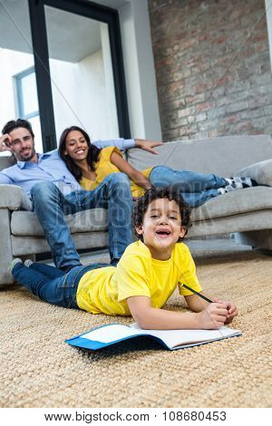 Smiling family in living room with son laying in the carpet while drawing