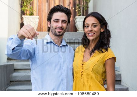 Happy Hispanic couple in front of new house showing keys