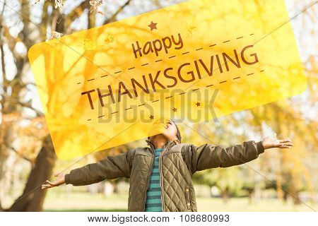 Happy thanksgiving against leaves drop onto a little boy with outstretched arms