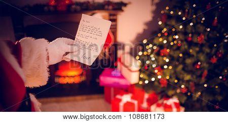 santas list against santa claus holding a paper