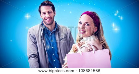 Smiling woman with shopping bag in front of cashier against blue background with vignette