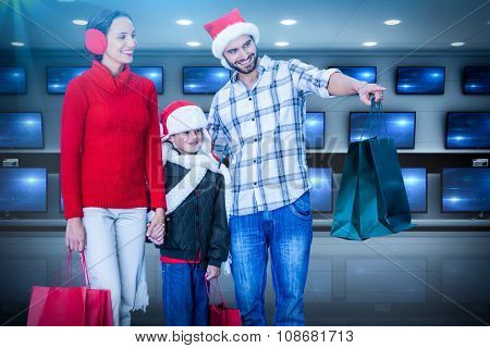 Happy family looking at camera against televisions for sale