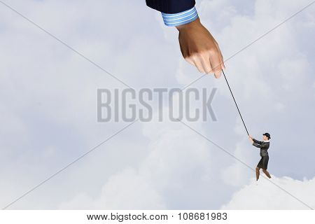 Young businesswoman in bowler hat pulling rope