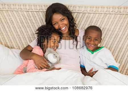Mother in bed with children at home