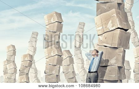 Young businessman and stack of carton boxes behind him