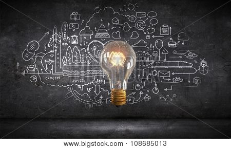 Glowing glass light bulb and business sketches at dark background
