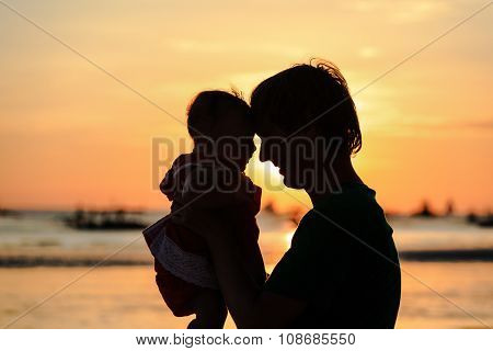 father and little daughter silhuettes on sunset beach