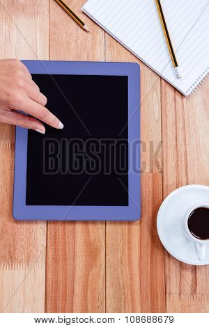 Overhead of feminine hand using tablet with black espresso and notebook on desk