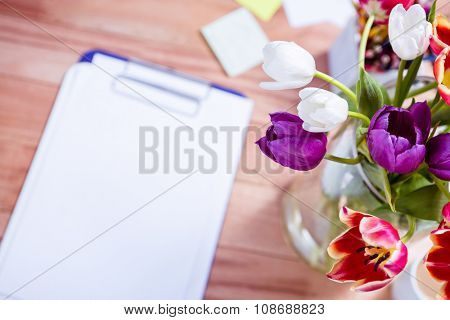 Bouquet of flower in a vase on the desk at work