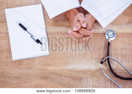 View of doctor with hands crossed on desk