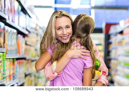 Smiling mother and daughter with grocery bag hugging at the supermarket