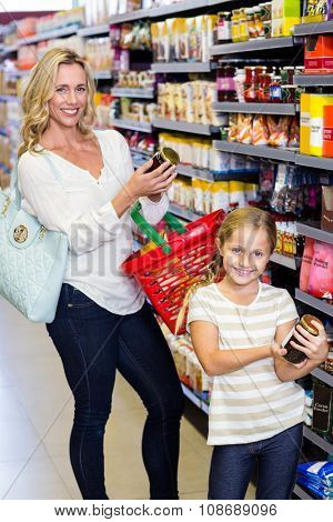 Mother and daughter reading nutritional values of products in supermarket