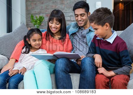 Happy young family reading a book together in living room