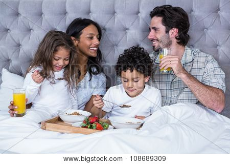 Happy family having breakfast on bed at home
