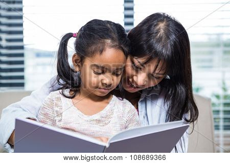 Happy mother reading book with her daughter in living room