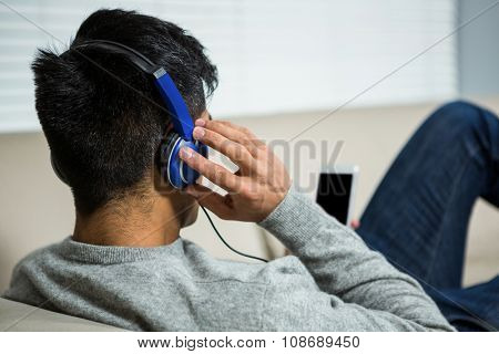 Over shoulder view of casual man listening music in living room