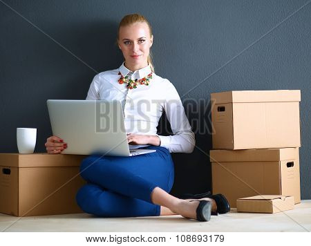 Woman sitting on the floor near a boxes  with laptop