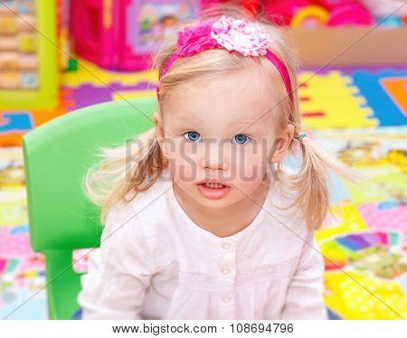 Portrait of cute adorable blond baby girl having fun in daycare, spending time in playroom, happy healthy childhood