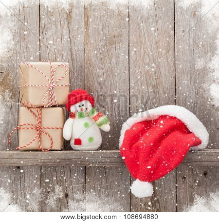 Christmas gift boxes, santa hat and snowman toy in front of wooden wall with copy space
