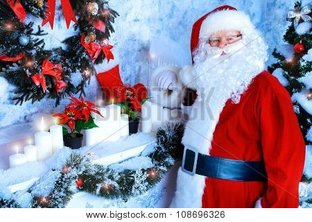 Jolly Santa Claus standing by the fireplace in a room, decorated for Christmas.