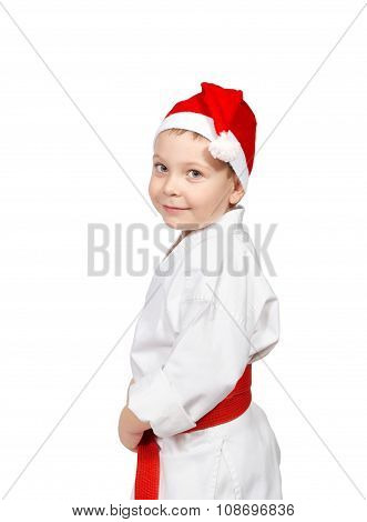 Little boy in a kimono with a red belt and cap of santa claus
