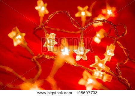 Star shaped Christmas lights on red background