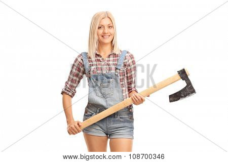 Blond female worker in jumpsuit and checkered shirt holding an axe and looking at the camera isolated on white background
