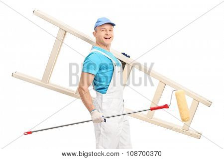 Young male decorator walking with a paint roller and a wooden ladder in his hands isolated on white background