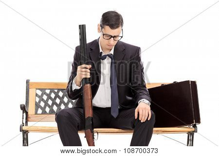 Depressed businessman holding a shotgun rifle and looking down seated on a wooden bench isolated on white background
