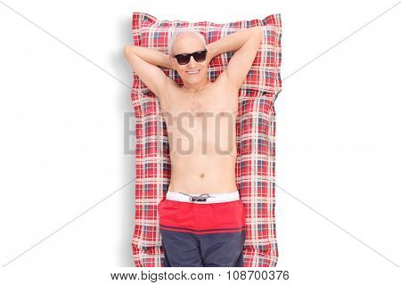 Relaxed senior lying on a swimming mattress and looking at the camera isolated on white background