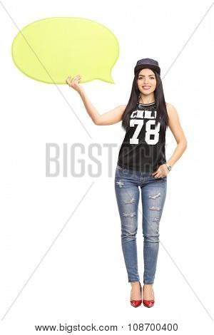 Full length portrait of a young woman in hip-hop clothes holding a yellow speech bubble and looking at the camera isolate on white background