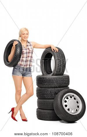 Full length portrait of a female mechanic holding a car tire and standing next to a stack of tires isolated on white background
